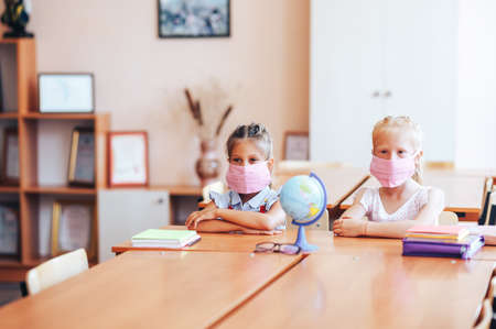 Two little schoolgirls sit at a desk in a school class in medical masks and carefully listen to the teacher. Stock Photo