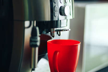 Close-up coffee machine making fresh coffee in the morning, coffee machine and red mug. Banque d'images