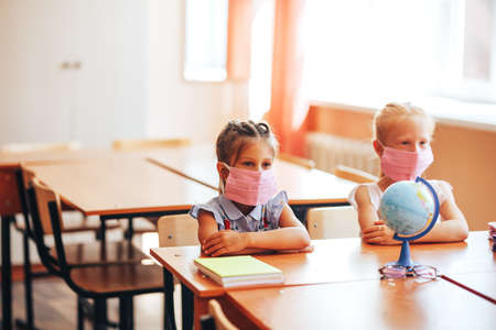 Two little schoolgirls sit at a desk in a school class in medical masks and carefully listen to the teacher