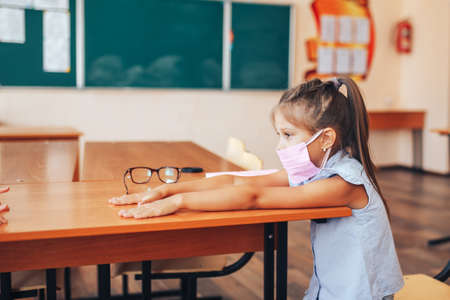 Two schoolgirls in medical masks are sitting at a school desk, opposite each other, group session, back to school, teaching children