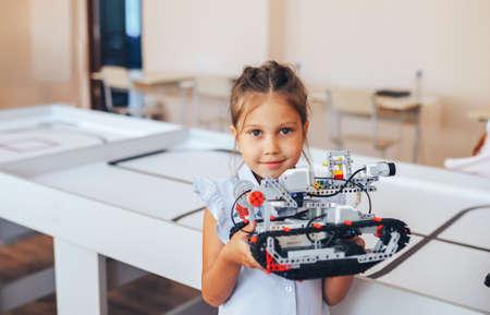 Schoolgirl holding constructor robot in robotics class