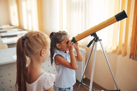Two schoolgirls are looking through a telescope in an astronomy lesson, back to school, childrens education