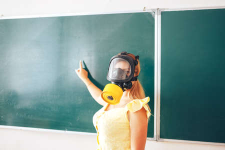 Young teacher in a medical mask holding a pointer in her hand and points to a white board, back to school, modern education, training during the epidemic