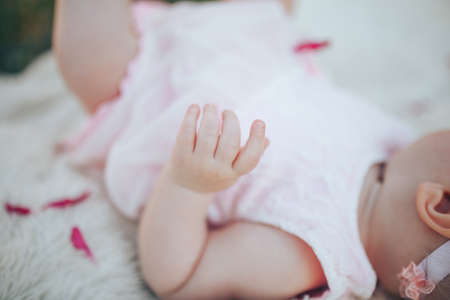 Little newborn baby in a pink dress on a white plaid in a park