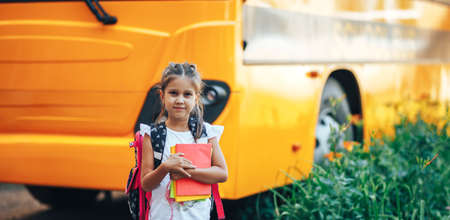 A schoolgirl with a backpack holding a book in her hands on the background of a school bus, back to school.