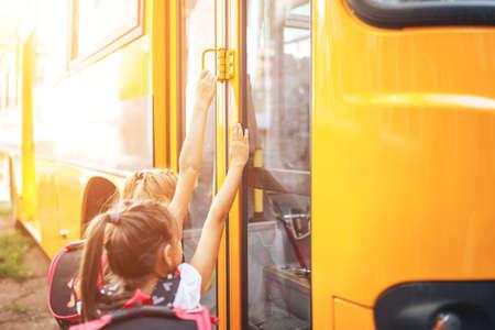 Schoolgirls with backpacks enter the school bus, back to school.