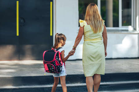 Mom holding the hand of her child, mom escorts her child to school, back to school, knowledge day.