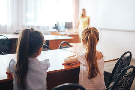 Two little schoolgirls sit at a desk in a school class and carefully listen to the teacher.