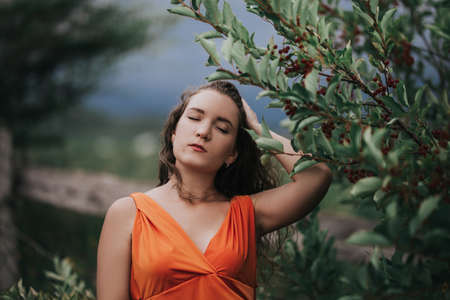 Girl in an orange dress on a background of a tree with fruits, portrait photo of a young girl.