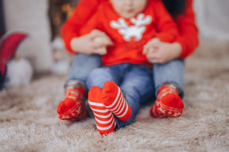 Mom holding her child by the hands sitting on a soft carpet in red sweaters and red socks, Merry Christmas and Happy New Year.