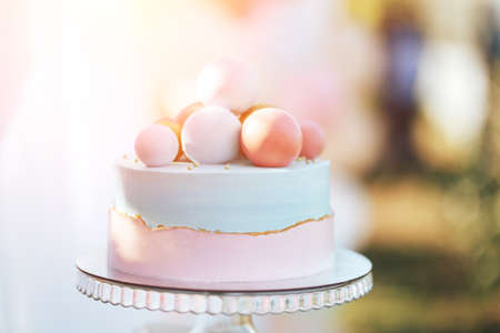Two-tier cake is two-tone, the bottom of the cake is pink and the top is blue, the cake has different balls. Standard-Bild