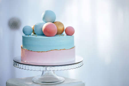 Two-tier cake is two-tone, the bottom of the cake is pink and the top is blue, the cake has different balls.