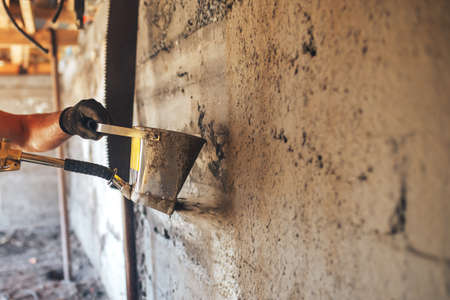 Man plastering a wall with mortar using a hopper bucket.