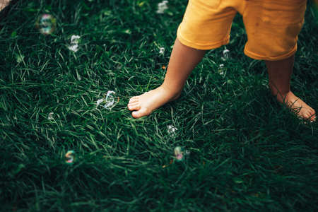 A small child standing barefoot on a green lawn, a child tramples soap bubbles with his feet.