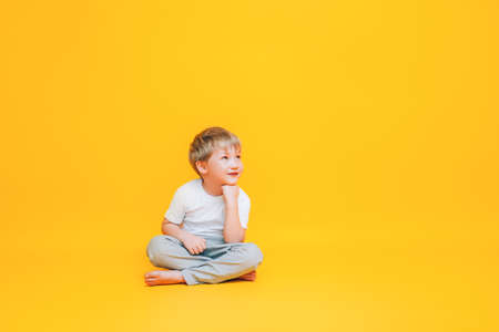 Pensive little boy in white t-shirt sitting on yellow background.