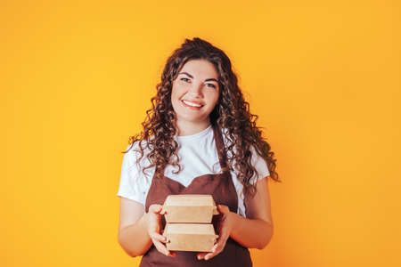 Young woman dressed in a catering uniform with outstretched arms, boxes of food in hands Banque d'images