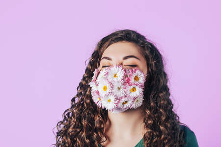 Young woman wearing a medical mask made of flowers during a pandemic