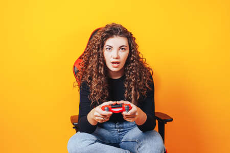 Woman sitting behind gaming chair in her hands holding red gamepad on yellow background.