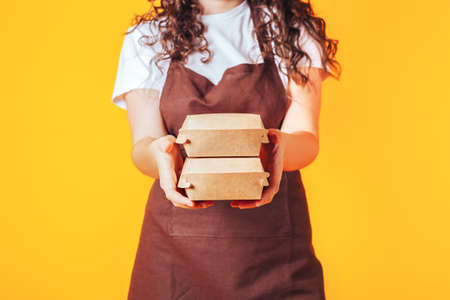 Young woman dressed in a catering uniform with outstretched arms, boxes of food in hands. 免版税图像