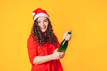 Young woman in red dress and christmas hat opens a bottle 版權商用圖片