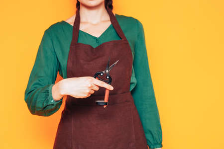 Young girl florist in a green sweater and brown apron on a yellow background, how to start a flower business 版權商用圖片