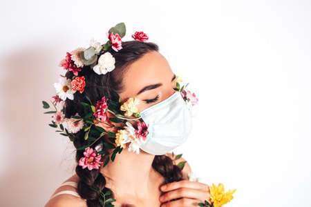 Beautiful nymph woman in a medical mask on a white background, in her hair she has flowers and a wreath of flowers