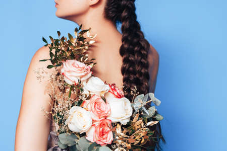 A young woman has a beautiful bouquet of roses on her back. 스톡 콘텐츠