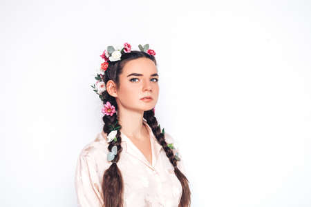 Young woman in a white shirt, different beautiful flowers are braided in her hair on a white background. spring time
