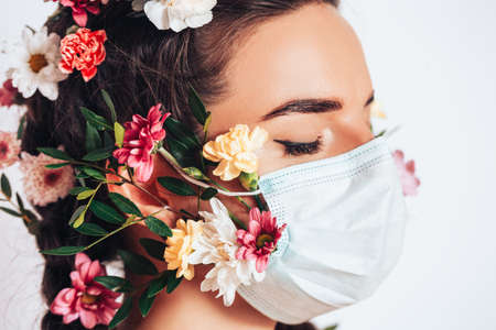 Beautiful nymph woman in a medical mask on a white background, in her hair she has flowers and a wreath of flowers.