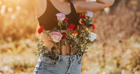 Young beautiful woman with long hair in nature, different types of flowers in jeans, female health concept, enjoying the fresh air. spring