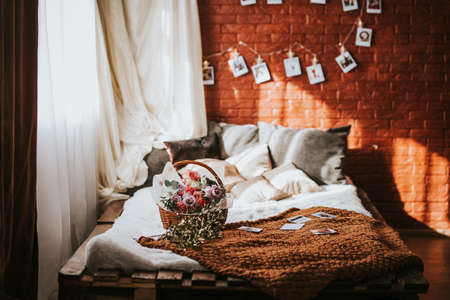 A large bed of pallets with pillows, on the bed there is a large basket of flowers of different types, a garland with photos on the brick wall, the sun's rays seeping through the window.