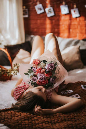 A young woman lies on a bed made of wooden pallets with flowers of different types, photos on a brick wall, the sun's rays seep through the window.