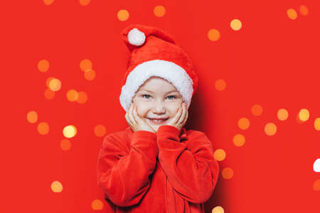 A little boy in a red Christmas costume, a red Christmas hat on his head, joyfully holds himself with his hands behind his face.