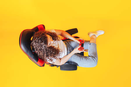 Woman sitting behind gaming chair in her hands holding red gamepad on yellow background, view from above.