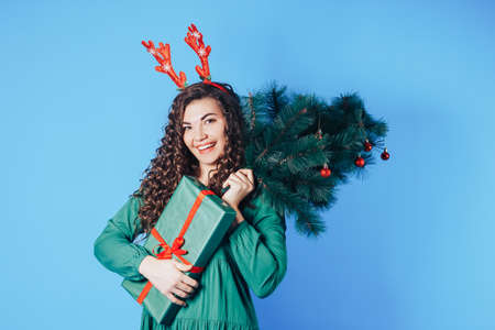 Young woman holding Christmas tree and box in her hands, she has a red deer horns on her head on a blue background.