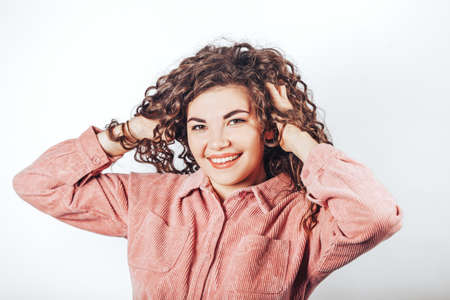 Beautiful woman with curly hair posing at camera on white background.