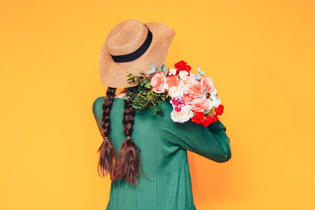 Young woman in green dress and wearing straw hat on her head put, on her shoulder beautiful mix of bouquet of different flowers on yellow background.