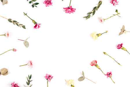 On a white background, flowers of different species are laid out in a circle, branches with beautiful leaves, blooming flowers and buds of flowers that have not opened.