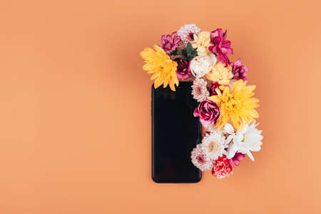 A mix of various colors next to a black phone, a gift for any occasion, a gift to a loved one on an orange background.