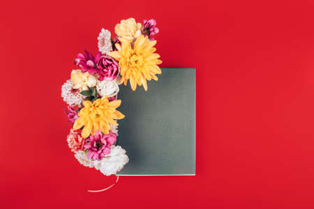 Mix of different colors next to a black notebook, a gift for any occasion, a gift to your loved one on a red background.