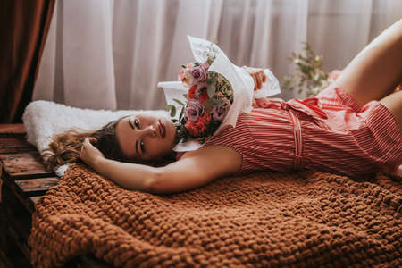 A young woman lies on a bed made of wooden pallets with flowers of different types, the sun's rays seep through the window.