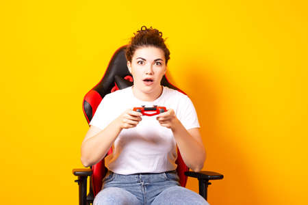 Woman playing video games while sitting on a gaming chair, free time activity, new hobby woman during self-isolation, woman in e-sports.