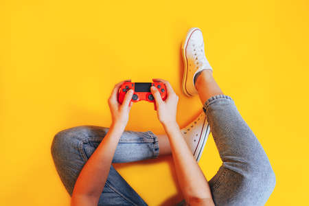 Woman holding gamepad in her hands in against of a yellow background. Promotion of women's esports. Advertising of esports equipment. Flat lay. Place for text. 版權商用圖片