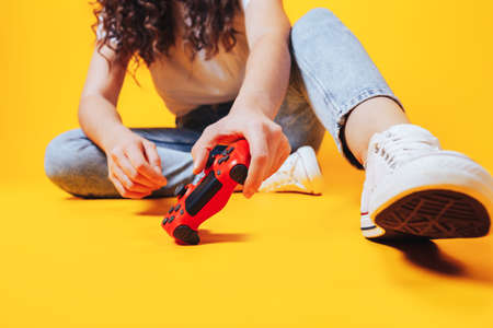 Woman holding gamepad in her hands in against of a yellow background. Promotion of women's esports. Advertising for the promotion of esports equipment. Place for text.