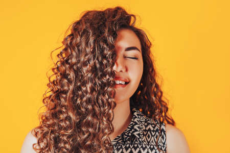 Young beautiful woman shows emotion pleasure. Beautiful curly hair. Advertising of a beauty salon and dentistry. Place for your text.