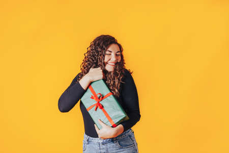 Woman holding large box in her hands. Gift in green packaging with red ribbon and red bow. Gift for woman for holiday or special occasion.