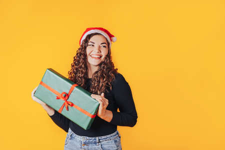 Woman holding box in green packaging with gift. Red santa hat is on his head. Expectation of presents for Christmas and new year. Place for your text.