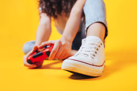 Woman holding gamepad in her hands in against of a yellow background. Promotion of women's esports. Advertising of esports equipment. Place for text.