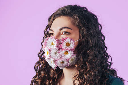 Young beautiful woman in protective mask of blooming flowers on pink background. Breathe fresh air. Contaminated air. 版權商用圖片