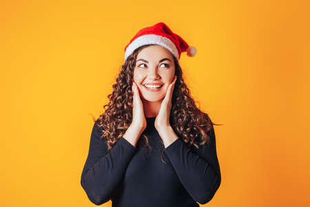 Beautiful woman with curly hair and a santa hat on her head. The woman smiles and touched her face with her hands. Christmas mood. Space for text on a yellow background. 版權商用圖片